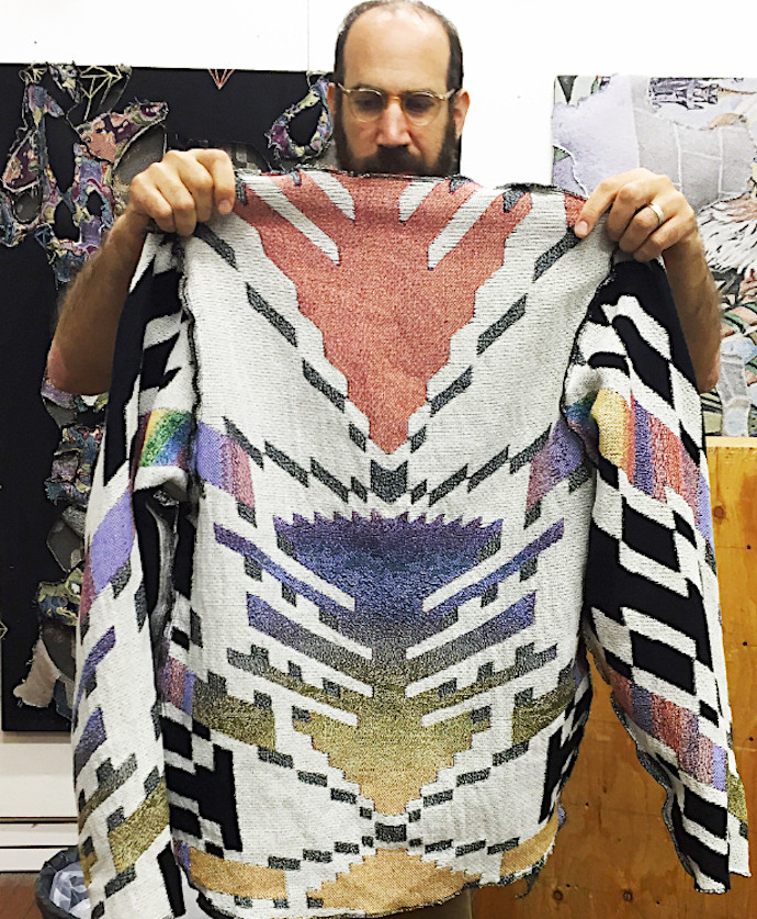 artist David Smith holds up one of his colorful blanket jackets; photo erica lewis